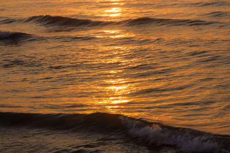 Sea at sunrise with golden tones of sun reflections in the water and waves