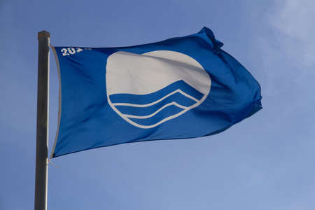 Blue flag of the year 2018. International symbol that identifies Beaches and Clean Ports and the trail of two planes crossing through the sky