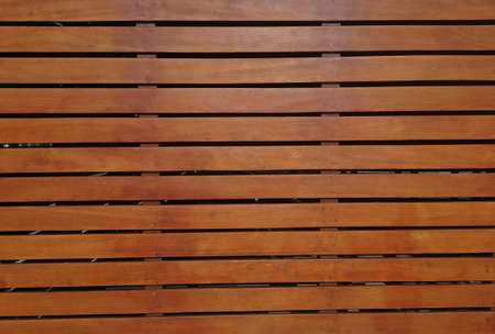 Textured background with floor surface or wall of varnished wooden boards in parallel with slacks