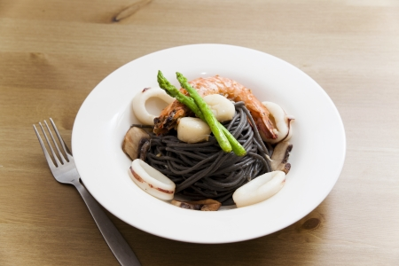 Black spaghetti with seafood on wooden table (squid ink pasta) Zdjęcie Seryjne