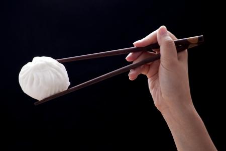 Chinese steamed bun with chopsticks (Dim Sum)