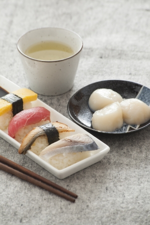 Japanese Sushi and Sashimi -- Egg, Tuna, Eel, Swordfish, Jumbo Scallop, Green tea photo