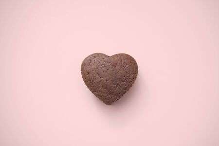 Chocolate Valentine Cake on pink background (heart shape) photo