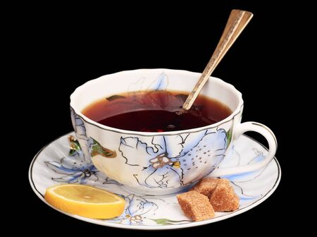 cup of tea on a saucer, brown sugar, a teaspoon  black background  photo