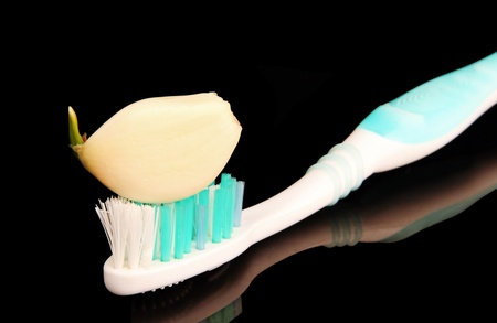 Toothbrush with garlic  reflection in the dark glass  background black Stock Photo - 16655771