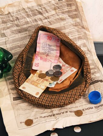 mendicant: Notes and coins in the cap beggar  newspaper on the sidewalk  empty bottle