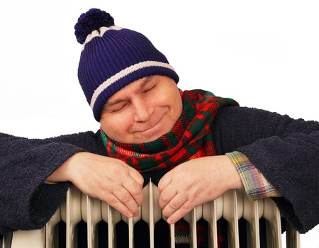 woolley: warmly dressed man warms himself at home oil radiator