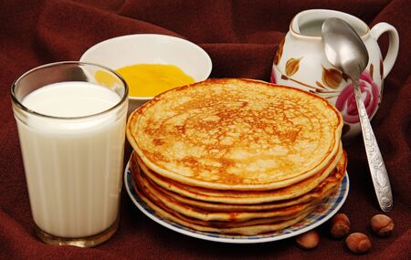pancakes with milk on a plate, a glass of milk, honey and nuts on a brown background  Stock Photo - 17154484