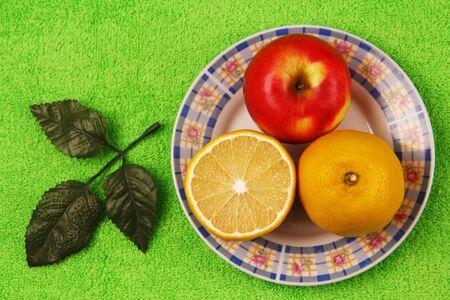 antipode: lemon, half a lemon and a whole apple lying on the plate