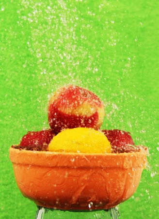apples and lemon in a ceramic cup under running water on a green background  photo