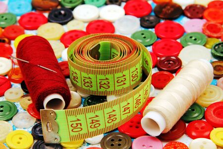 sewing thread, needle, sartorial meter on the background of buttons in different colors  photo