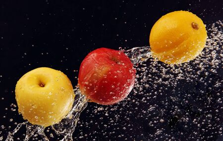 two apples and a lemon in a stream of pure water, a dark blue background Stock Photo - 17699911