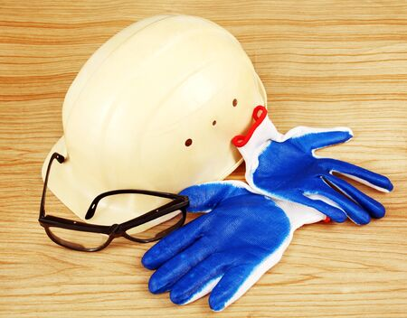 white construction helmet, goggles and blue gloves on a wooden surface  photo