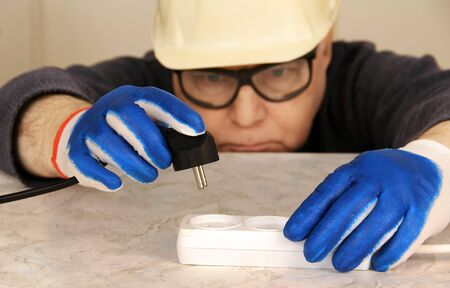 worker in protective helmet, gloves and glasses inserts an electric plug  Stock Photo - 18453054