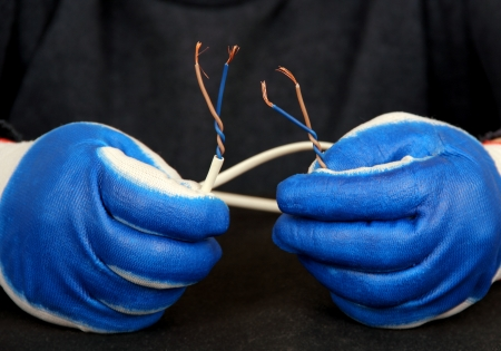 bare wire: working hand in glove holding the electric wire with bare ends