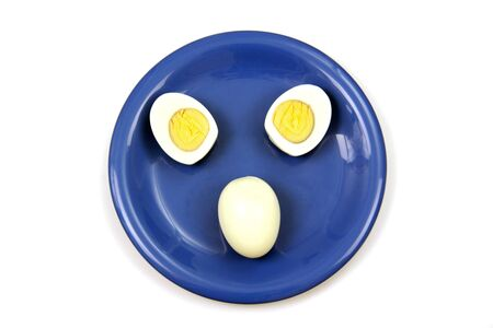 animal origin: one whole egg and two egg halves lie on blue porcelain plate, photo on the white background
