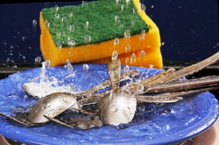 fork, spoon and table knife on blue plate under running water