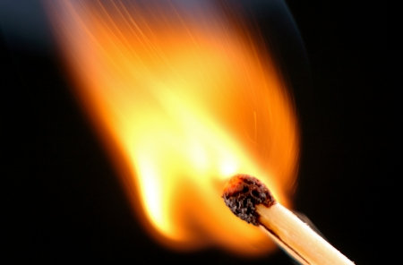 burning matches, fire and curls of smoke, a photo close up on a black background. Фото со стока