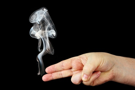 smoke from the fingers of a hand depicting a gun, a photo on a black background. photo