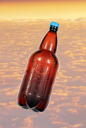 brown beer bottle covered with water drops on a background of orange sunset clouds  photo