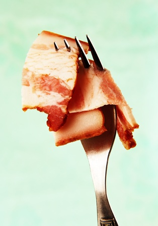 a thin slice of ham slice on a metal fork on a pale blue background  photo