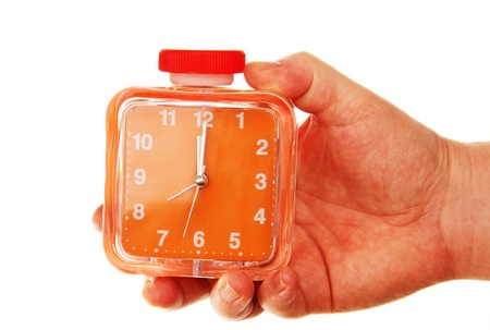 alarm clock orange in male hands, photo on the white background  photo