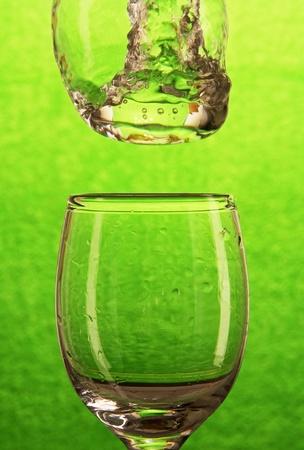 welling: flusso di acqua che cade in un bicchiere trasparente con gocce e spruzzi, sfondo verde