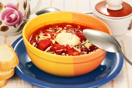 vegetable soup with tomato red color in yellow porcelain cup on a blue plate  Stock Photo - 20326242
