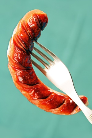 grilled sausage with cuts on the metal fork, blue background. photo