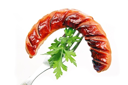 grilled sausage with parsley leaves on a metal fork, white background. Standard-Bild