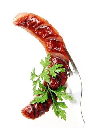 grilled sausage with parsley leaves on a metal fork, white background. photo