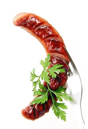 saucisse: saucisse grill�e avec les feuilles de persil sur une fourchette en m�tal, fond blanc. Banque d'images