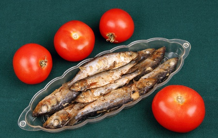 small fried fish and cut into rings of tomatoes on a slice of bread  photo