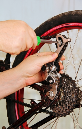hand of the master with a wrench, repair a bicycle wheel