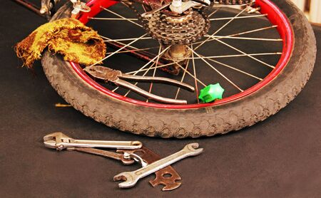 rear wheel of a bicycle on a dark background, tools and supplies for repair  photo