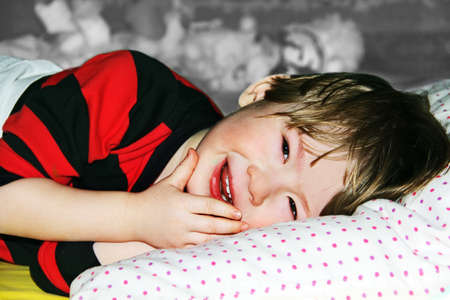 smiling little boy lying on a bed with his eyes open. photo
