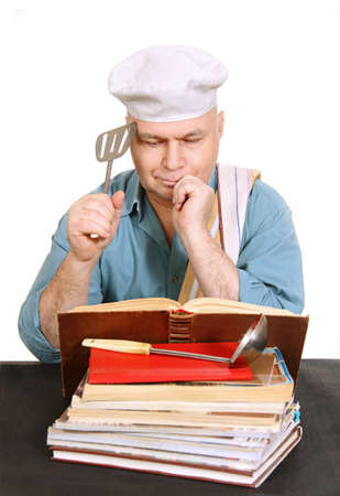 cook man looking for a recipe in the cook book, white background. photo