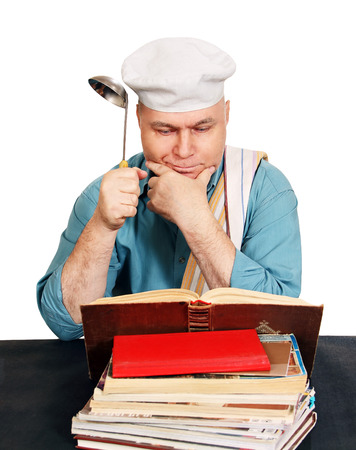 cook man looking for a recipe in the cook book, white background. Standard-Bild