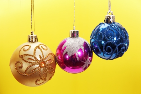 three colored glass Christmas tree ball, photo on the yellow .  photo