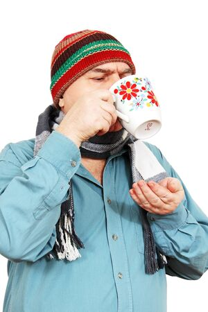 a grown man wearing a scarf and hat with a cup of tea in hand, white .  photo
