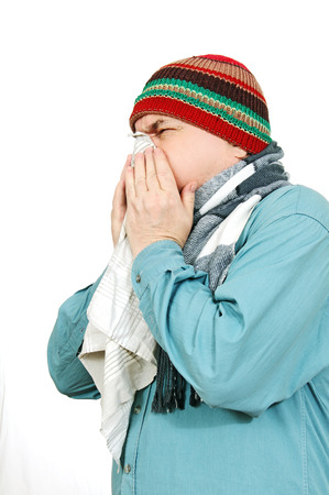 man in warm hat and scarf blowing his nose into a handkerchief, white . photo
