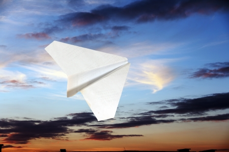 childrens paper airplane flying against the sky and clouds.