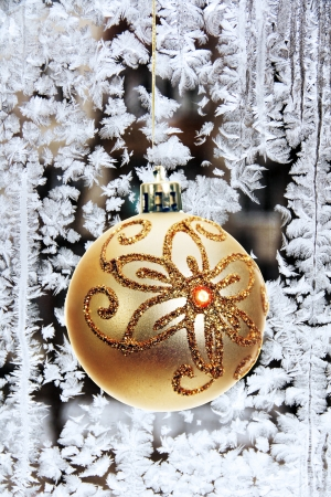 Christmas tree toy on the background of frost patterns on a window pane.  Фото со стока
