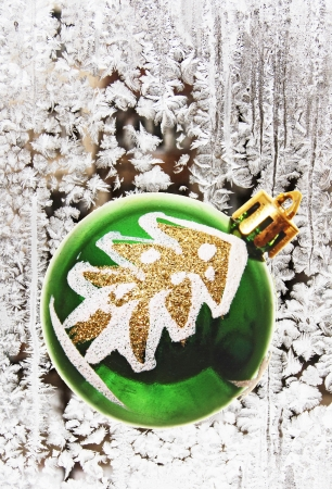 Christmas tree toy on the background of frost patterns on a window pane.