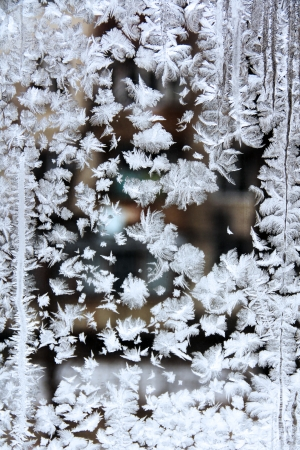 window glass, decorated with winter frost patterns of various shapes. Standard-Bild