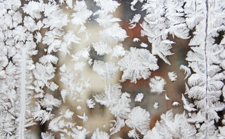 window glass, decorated with winter frost patterns of various shapes.