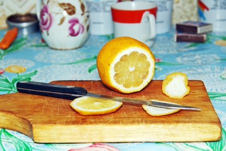 sliced ??lemon and knife on a wooden board, kitchen utensils in the background.