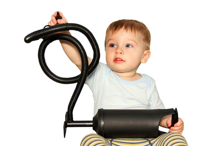 little boy playing with a hand pump on an inflatable mattress, a photo on a white background.