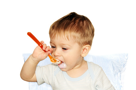 mothers hand feeding a young child from a red plastic spoon.