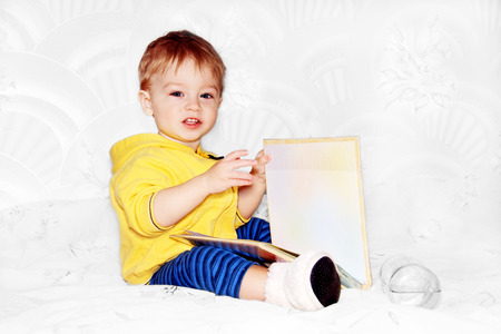 little boy flips through a large book sitting on the couch. Standard-Bild